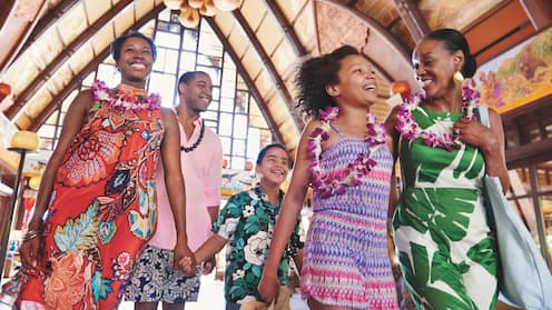 A multi-generational family wearing flower and kukui nut leis, walks through the main lobby at Aulani Resort