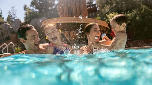 A family of 4 enjoys the pool at Disney's Grand Californian Hotel & Spa