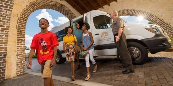 A family of 4, including a young boy wearing a Mickey Mouse tee shirt, get out of a Golden Oak van in a portico as the driver stands nearby