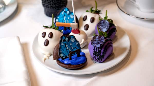 A plate of Haunted Mansion themed treats including chocolate covered strawberries