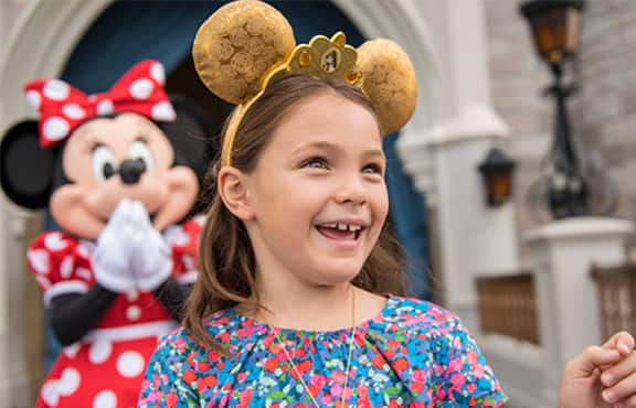 A smiling young girl walking away from Minnie Mouse