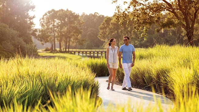 A romantic couple strolls arm in arm along an outdoor path through tall grasses at sunset