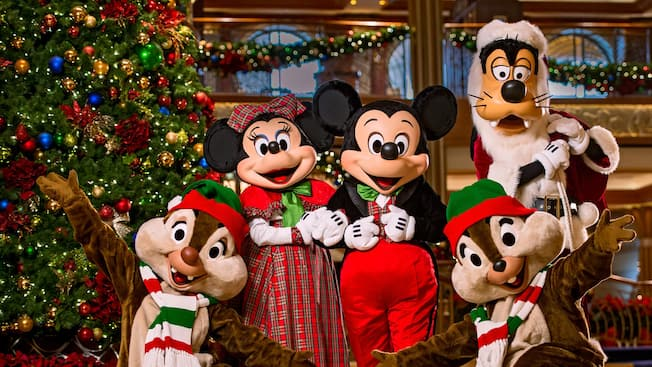 Mickey Mouse, Minnie, Goofy and Chip and Dale posing in front of a Christmas tree