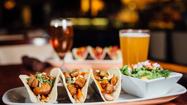 A glass of draft beer and a platter featuring 3 Short Rib Tacos and a salad