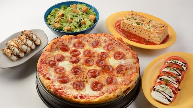 A pepperoni pizza served with salad, pasta and cannolis.