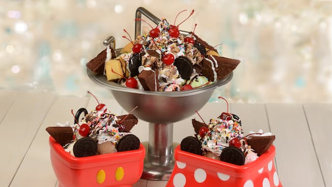 A kitchen sink and 2 smaller containers filled with ice cream, hot fudge, sprinkles, whipped cream and cherries