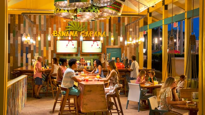 A bar with 2 TVs displayed on the wall, a sign that says Banana Cabana, a communal table and other tables with Guests sitting and eating