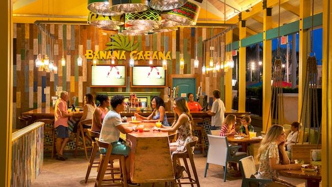 Un bar avec 2téléviseurs sur le mur, une enseigne indiquant Banana Cabana, une table commune et d'autres tables avec des visiteurs assis qui mangent