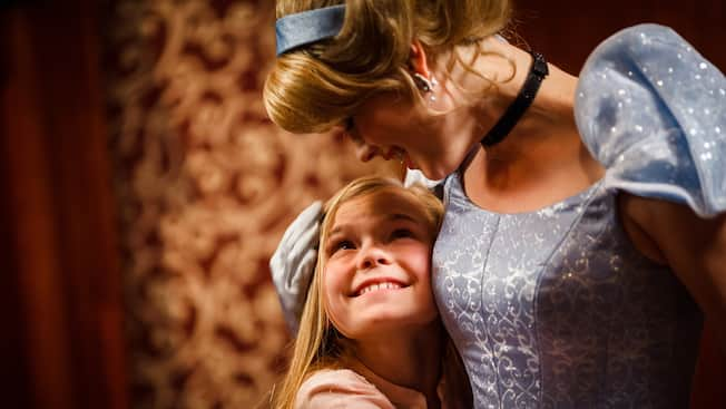 A little girl smiles up at Cinderella as she gives her a hug
