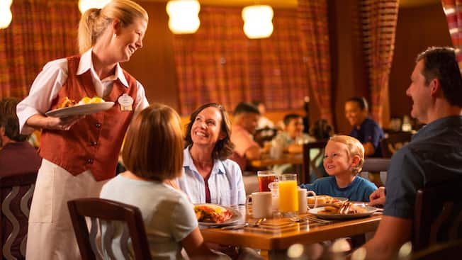 A waitress serves a family at The Wave of American Flavors