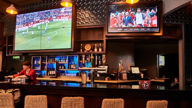 A bartender tending an upscale bar with large TV screens