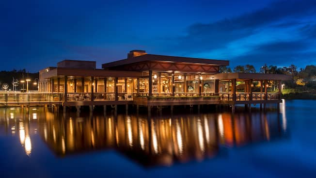 The outside of the Three Bridges Bar & Grill on Lago Dorado at night, its lights reflecting off the water.