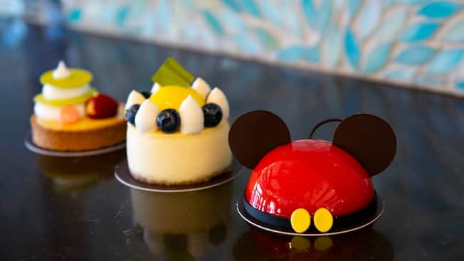Three delightful circle shaped pastries, including one that looks like Mickey Ears, one cheesecake with whipped cream and fruit toppings, and one tart topped high with fruit and whipped cream