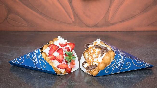 Two bubble waffles in Aristocrepes wrappers laying side by side, one is filled with strawberries and whipped cream, the other with chocolate ice cream, chocolate covered pretzels and whipped cream swirled with caramel