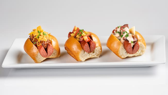 Three mini hot dogs on a plate, topped with chili, diced spam and pineapple salsa or corned beef