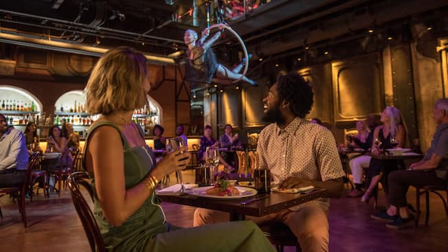 A couple at a dining table enjoying a performance by an aerialist