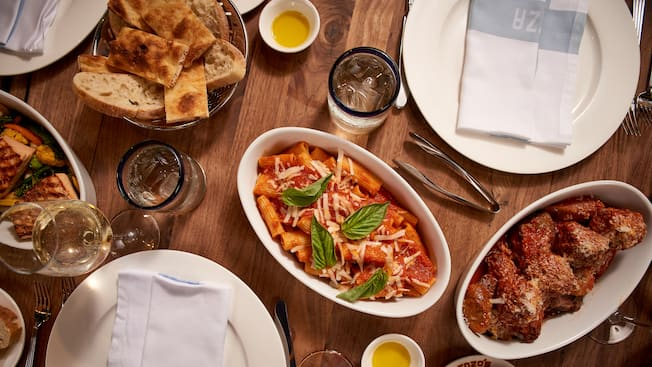 A dish of baked rigatoni on a dining table beside a dish of short ribs and a basket of bread