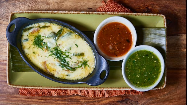 A melted cheese dish with roasted poblanos and caramelized onions is served with 2 types of salsa