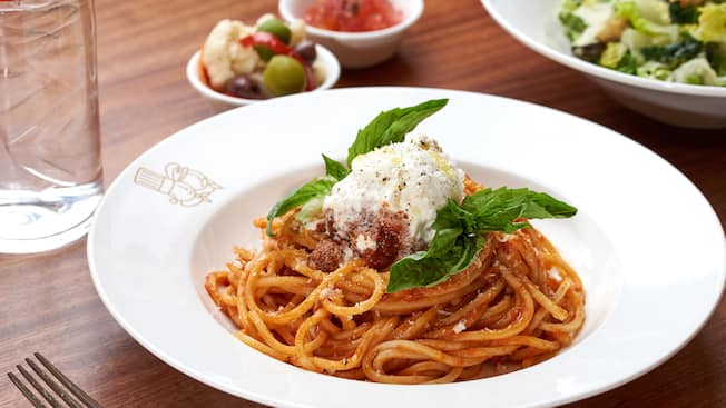 A plate of spaghetti with a side salad