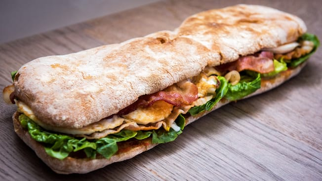 A long sandwich with thin bread, bacon, lettuce and other ingredients