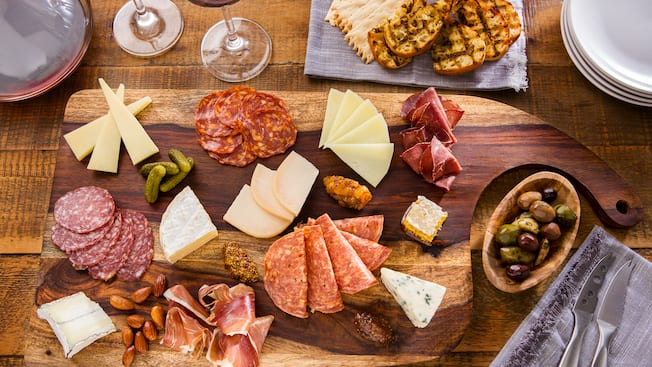 A table with wine, plates, a bowl of olives, cheese knives and a charcuterie board of cheese and meats