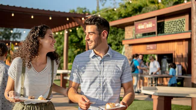 A man and woman smile at each other while holding desserts outside at Epcot