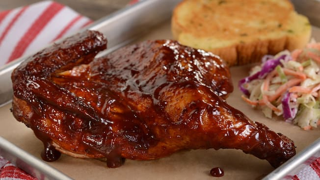 Chicken covered in barbecue sauce next to a piece of toast