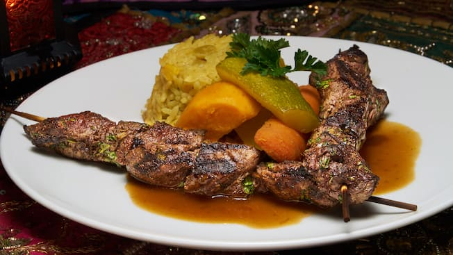 2 beef shish kebabs served with yellow rice and mixed vegetables