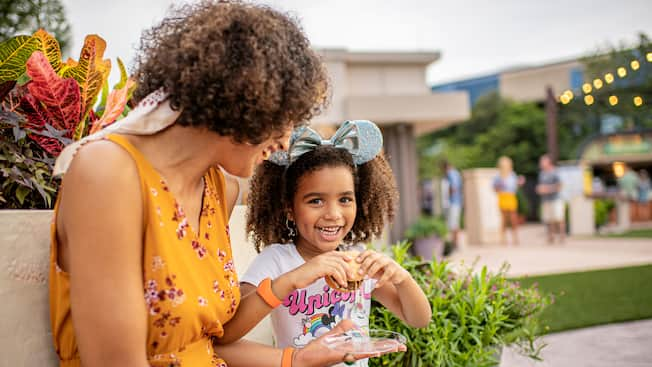 Mom and young daughter enjoy Epcot festival food on a bench