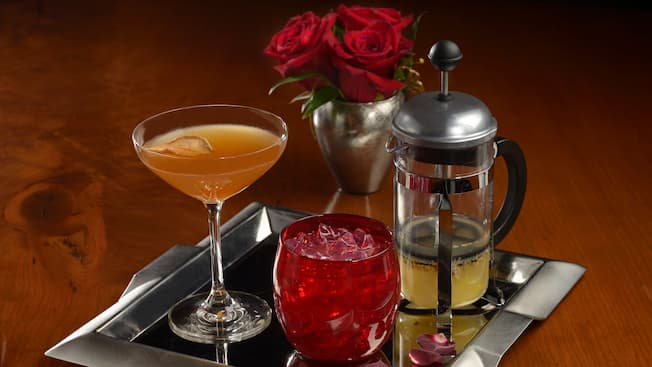 Three beverages being served on a tray next to a bouquet of roses