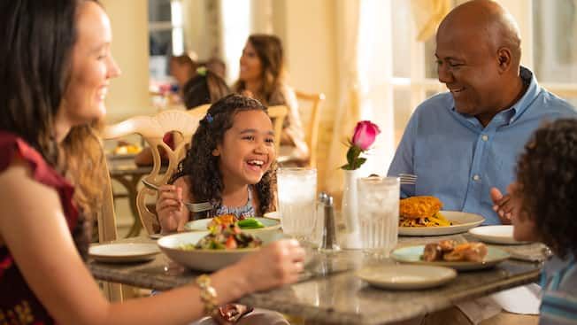 A family shares a laugh, dining together in Grand Floridian Café at Walt Disney World Resort