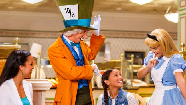 The Mad Hatter and Alice interact cheerfully with a girl while her mother looks on