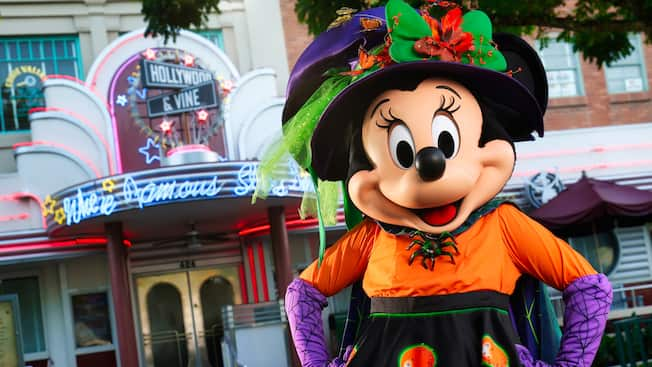Minnie Mouse poses in formal Halloween attire in front of Hollywood and Vine
