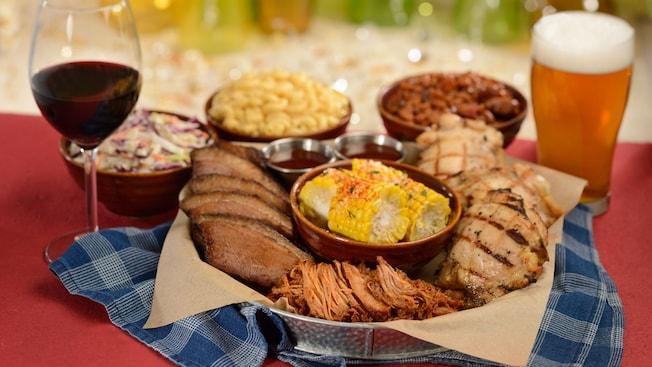 Mazorca de maíz, falda de res, pollo asado, cerdo desmenuzado, frijoles horneados y ensalada de repollo, servido con bebidas