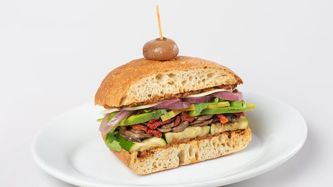 A vegetarian sandwich featuring summer squash, mushrooms, grilled red peppers, avocado, grilled onions, cheese and tapenade
