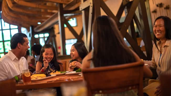 A family dines in Boatwright's Dining Hall, a restaurant decorated with boat frames