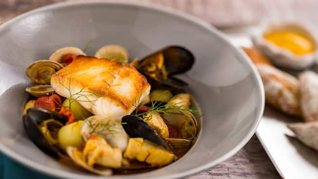 A bowl of bouillabaisse featuring mussels, clams and white fish