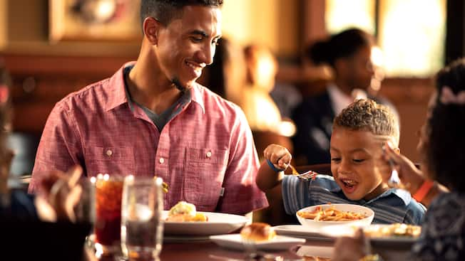 A father smiling at his young son while enjoying breakfast in a restaurant