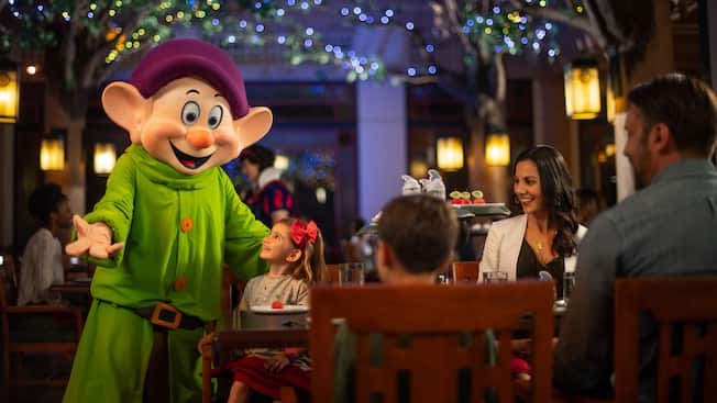 A little girl smiles up at Dopey while sitting with her parents and brother at a table