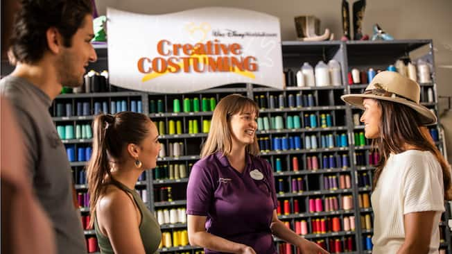 A group of people speak with a Cast Member near a wall of thread and craft supplies at Walt Disney World Resort's Creative Costuming