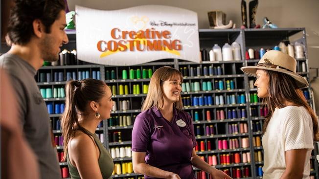 Un grupo de personas conversa con un Miembro del Elenco cerca de una pared con hilos y materiales de artesanía en Walt Disney World Resort's Creative Costuming