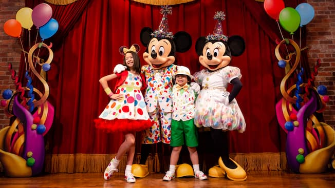 Dressed in party costumes, Mickey Mouse and Minnie Mouse pose with pair of young Guests on a stage