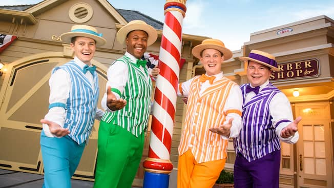 A barbershop quartet near a pole and storefronts