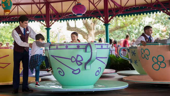 A Tour Guide helps a little boy into a Mad Tea Party tea cup
