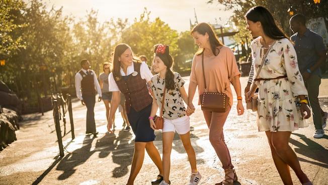 Uma guia Disney acompanha um jovem Visitante e 2 Visitantes adultos pelo Magic Kingdom Park