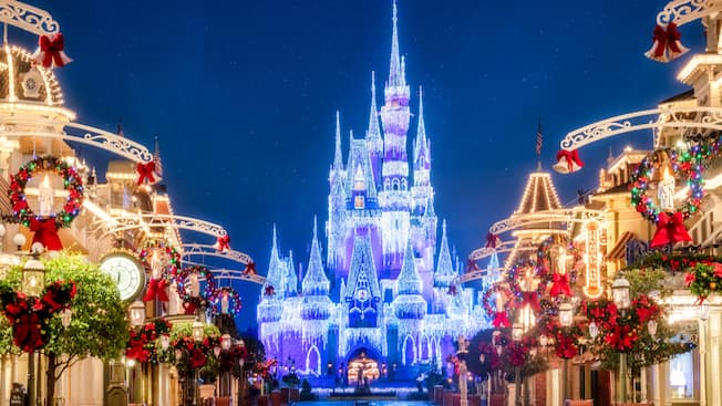 Cinderella Castle shining at nighttime under the glow of holiday lights at the end of Main Street U S A decorated with Christmas decor