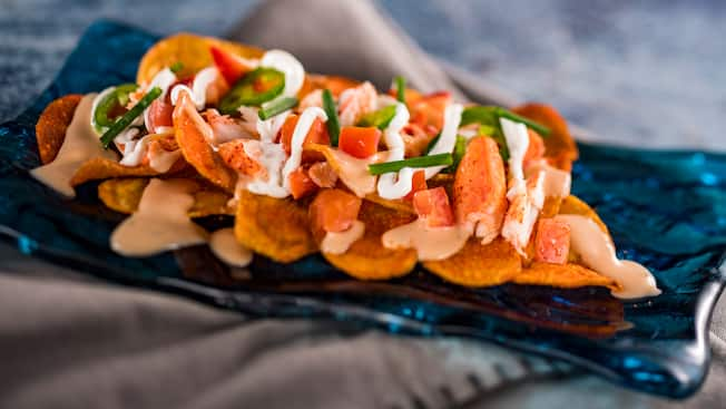 Chips topped with lobster, sauce and veggies
