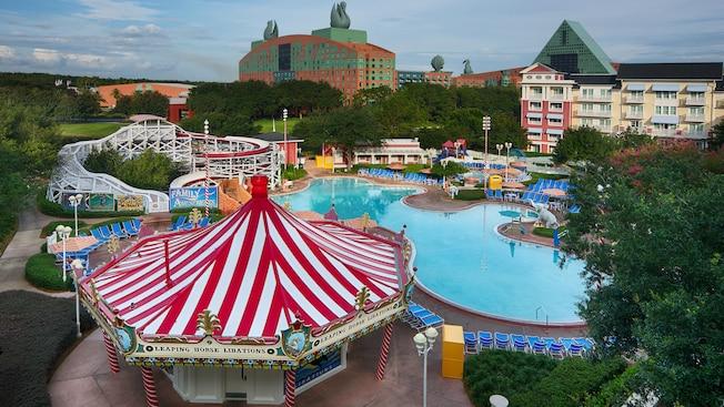 A área da piscina do Disney's BoardWalk Inn com 2 edifícios de vários andares, árvores exuberantes, uma lanchonete em formato de carrossel e um tobogã aquático que se parece com uma montanha-russa