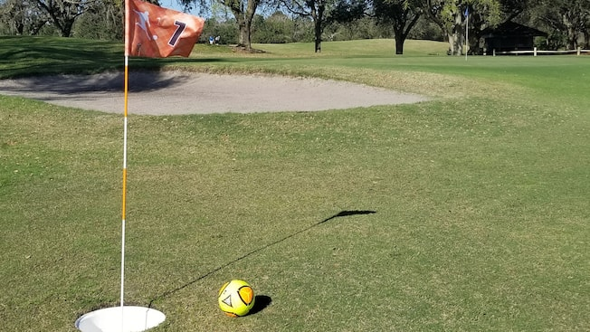A soccer ball near a sand hazard on a FootGolf course