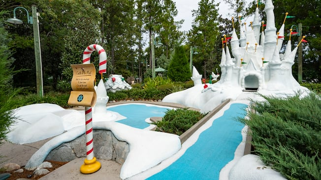 A miniature golf course hole featuring Cinderella Castle made of faux snow at Disneys Winter Summerland Miniature Golf Course